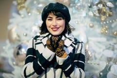 Bilden av den lyckliga brunetten går på bredvid dekorerad vit gran royaltyfria foton