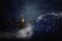 Bilden av den magiska mystiska aladdinlampan med blänker gnistranderök över svart bakgrund Lampa av önska royaltyfri foto