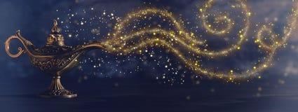 Bilden av den magiska mystiska aladdinlampan med blänker gnistranderök över svart bakgrund Lampa av önska arkivfoto