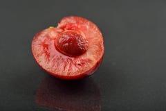 Bilden av den nya enkla körsbäret klippte i halva med kärnan i den isola Royaltyfria Foton