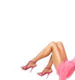 Bilden av den slanka kvinnlign lägger benen på ryggen bärande röda stilfulla skor på höga häl på vit bakgrund, trendigt skodon, l Fotografering för Bildbyråer