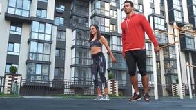 Bilden av den unga caucasian sportiga man- och kvinna20-tal i träningsoveraller som gör genomkörare och tillsammans squatting i g stock video