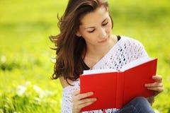 Bilden av den unga härliga kvinnan i sommar parkerar att läsa en bok royaltyfria foton
