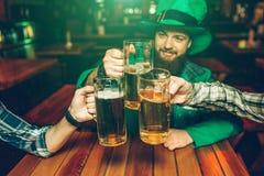 Bilden av den unga mannen i gröna Sts Patrick dräkt sitter på tabellen med vänner i bar De rymmer rånar av öl tillsammans royaltyfria foton