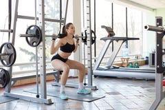 Bilden av den yrkesmässiga idrottskvinnan som gör övning i idrottshallen, squats med skivstången, lyfter vikter, framkallar s fotografering för bildbyråer