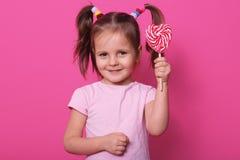 Bilden av det söta härliga kvinnliga barnet som rymmer den stora klubbagodisen, ser lycklig och spännande över rosa bakgrund, lit royaltyfria foton