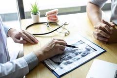 Bilden av doktorn eller tandläkaren som framlägger med tandröntgenstrålefilmen, rekommenderar tålmodig i behandlingen av tand- oc arkivfoto