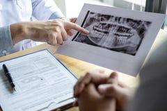 Bilden av doktorn eller tandläkaren som framlägger med tandröntgenstrålefilmen, rekommenderar tålmodig i behandlingen av tand- oc arkivbilder