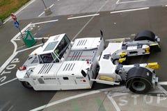 Bilden av en van vid flygplatstraktor skjuter nivåer till att parkera springor eller till landningsbanor Mycket kraftig flygplats royaltyfri fotografi