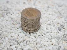 Bilden av högen av två euromynt på vita små stenar stänger sig upp royaltyfri fotografi