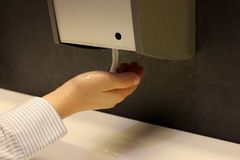 Bilden av handen använder en renande utmatare för vätska från en automatisk ask royaltyfri bild
