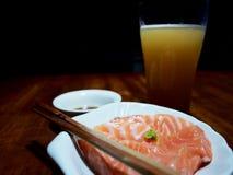 Bilden av laxsashimien, shoyusås och öl på wooden Royaltyfri Bild