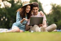 Bilden av mannen och kvinnan som sitter på gräs parkerar in, och använder bärbara datorn arkivfoto