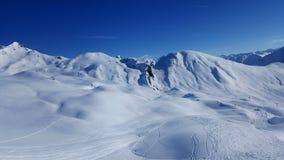 Bilden av skidar semesterorten i vintern med snö täckte berg och diskvatten royaltyfria foton