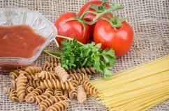 Bilden av tomater och rått helt vete röra sig i spiral pasta och spagetti Arkivfoto