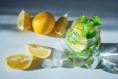Bilden av vatten med skivade sidor för citronen och för mintkaramellen för ‹för †i ett genomskinligt exponeringsglas rånar royaltyfri bild