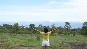 Bilden bak kvinnorna lyfter deras armar som ses bergen och träden på den Phu Hin Rong Kla nationalparken, Phetchabun lager videofilmer