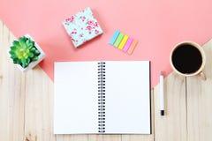 Bilden för den bästa sikten av den öppna anteckningsboken med tomma sidor, tillbehör och kaffekoppen på träbakgrund, ordnar till  Arkivbilder