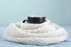 Bilden för den bästa sikten av den vita slags tvåsittssoffa stack tröjan med till koppen kaffe på en trätabell Royaltyfri Fotografi