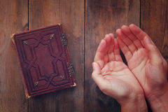 Bilden för den bästa sikten av mans händer vikta i bön bredvid bönboken begrepp för religion, andlighet och tro Fotografering för Bildbyråer