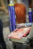 Bilden Sie Ausrüstung. Paletten des Lidschattenabschlusses oben mit Haarspray auf Hintergrund Lizenzfreie Stockfotografie