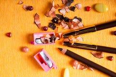 Bilden Sie Bleistifteyeliner mit einem Bleistiftspitzer nahe bei ihm auf gelbem papper Hintergrund Stockfotografie