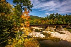 Bilden Sie Brücke über einer Fluss- und Herbstfarbe nahe Kirche, Maine aus stockbilder