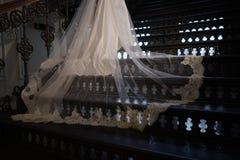 Bilden Sie das Hochzeitskleid aus, das auf der Eisentreppe liegt Stockfotos