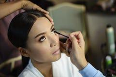 Bilden Sie den Künstler, der auf Wimperntusche auf schönem asiatischem Modell sich setzt lizenzfreies stockfoto
