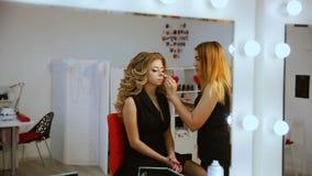 Bilden Sie den Künstler, der Berufsmake-up der jungen Frau nahe dem Spiegel im Schönheitsstudio tut stock video