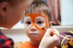 Bilden Sie den Künstler, der Tigermaske für Kind macht Kindergesichtsmalerei Junge gemalt als Tiger oder wilder Löwe lizenzfreie stockfotografie