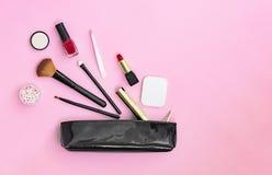 Bilden Sie die Produkte, die aus heraus schwarze lackierte Kosmetik verschüttet werden, sich bauschen auf einem rosa Pastellhinte stockfotografie