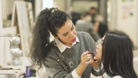 Bilden Sie Künstlerfarbenfrau ` s Lippen mit Lippenstift stock video footage