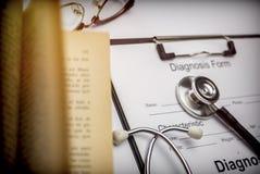 Bilden Sie sich von der Diagnose nahe bei einem alten Arbeitsbuch zu einem Stethoskop lizenzfreies stockfoto