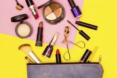 Bilden Sie Tasche mit Kosmetik auf gelbem und rosa Hintergrund stockfotos