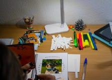 Bilder auf dem Schreibtisch und dem Schnitt sie betrachten stockbild