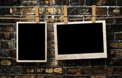 Bilder auf einem Seil mit Wäscheklammern, mit Beschneidungspfad für Bilder, vor einer Backsteinmauer Lizenzfreie Stockbilder
