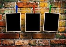 Bilder auf einem Seil mit Wäscheklammern, mit Beschneidungspfad für Bilder, vor einer Backsteinmauer Lizenzfreie Stockfotografie
