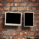 Bilder auf einem Seil mit Wäscheklammern, mit Beschneidungspfad für Bilder, vor einer Backsteinmauer Stockbild