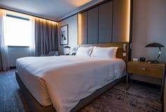 Bilder av ett generiskt hotellrum - säng, fönster, tabell, lampor som är alla i skott royaltyfria foton