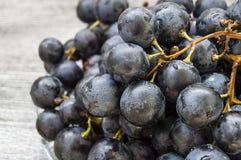 Bilder av svarta druvor på druvabilder för ett trägolv, svart- och gräsplani plattan, de stora svarta druvorna Royaltyfri Bild