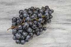 Bilder av svarta druvor på druvabilder för ett trägolv, svart- och gräsplani plattan, de stora svarta druvorna Arkivbild