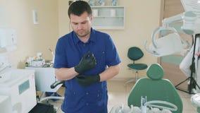 Bildern von jungen Doktor ` s Porträts einen Mann in seinem zahnmedizinischen Büro langsam nehmen bereitet vor sich, einen Patien stock video