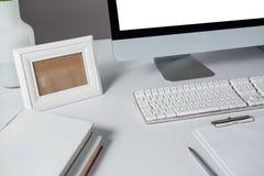 Bilderrahmen, Arbeitsplatzrechner und Bücher auf Tabelle Lizenzfreies Stockfoto