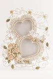 Bilderrahmen mit zwei Herzen mit zwei Tauben und kleinen Rosen Lizenzfreie Stockfotos