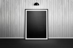 Bilderrahmen-Modell Feld, das auf weißer hölzerner Wand sich lehnt Stockfoto