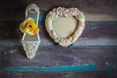 Bilderrahmen und Blumen auf hölzernem Stockbild