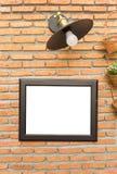 Bilderrahmen und klassische Lampe auf Backsteinmauer Lizenzfreie Stockbilder