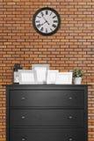 Bilderrahmencollagen auf schwarzem hölzernem Kabinett und Uhr in emp stockfotografie
