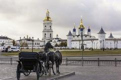 Bildhauerische Zusammensetzung mit einem Wagen zog durch ein Pferd auf dem Hintergrund des Tobolsk der Kreml. Russland stockfotos
